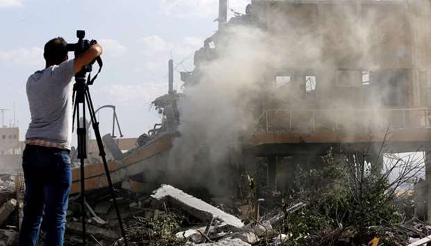 A journalist films the wreckage of a building described as part of the Scientific Studies and Resear
