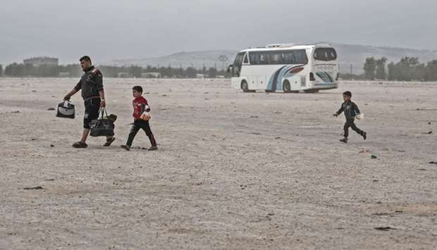 Members of a Syrian family evacuated from the town of Dumayr, east of the capital Damascus, carry th
