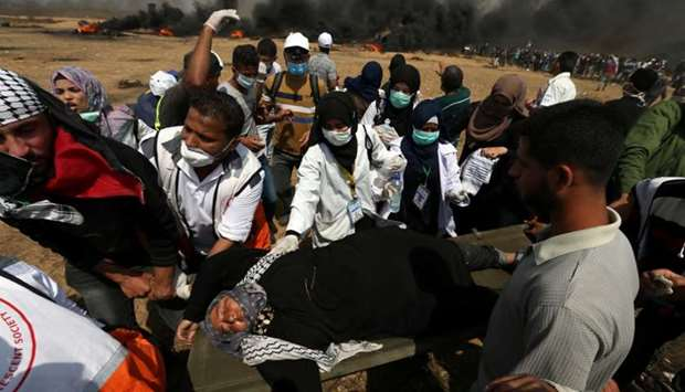 A woman demonstrator is evacuated after inhaling tear gas fired by Israeli troops in Gaza