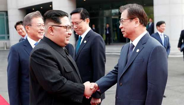 North Korean leader Kim Jong Un shakes hands with Suh-hoon, South Korea's chief of the National Inte