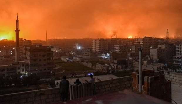 People stand on a roof to observe explosions in the skyline of a southern district of the Syrian cap