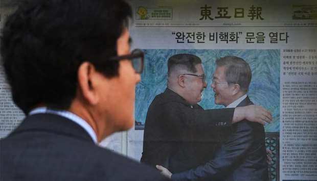 A man walks past a newspaper featuring a front page story about the summit between South Korean Pres