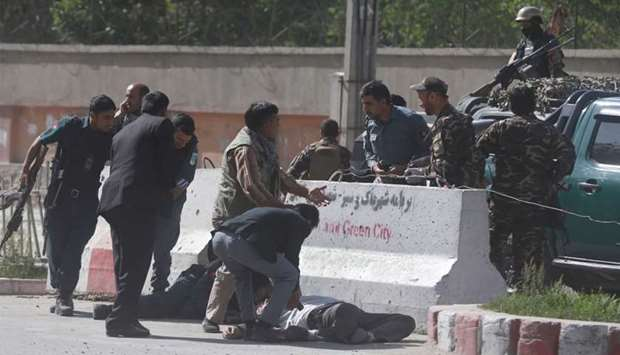 Policemen help Afghan journalists, victims of a second blast, in Kabul