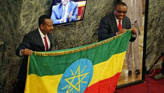 Ethiopia's new Prime Minister Abiye Ahmed and outgoing  Prime Minister Hailemariam Desalegn hold the