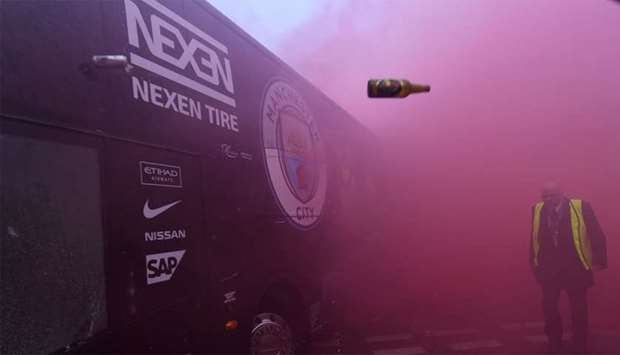 Bottles and cans are thrown at the bus as Manchester City players arrive at the stadium before the U