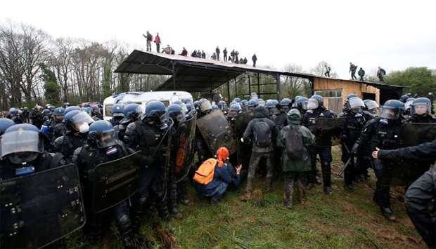 French gendarmes block a small group of protesters as others take position on the roof of a structur