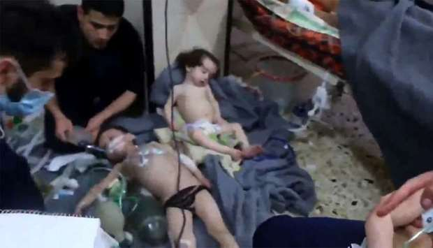 An image grab shows volunteers giving aid to children at a hospital following a reported chemical at