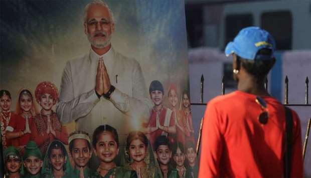 "A man looks at the poster of upcoming film ""PM Narendra Modi"""