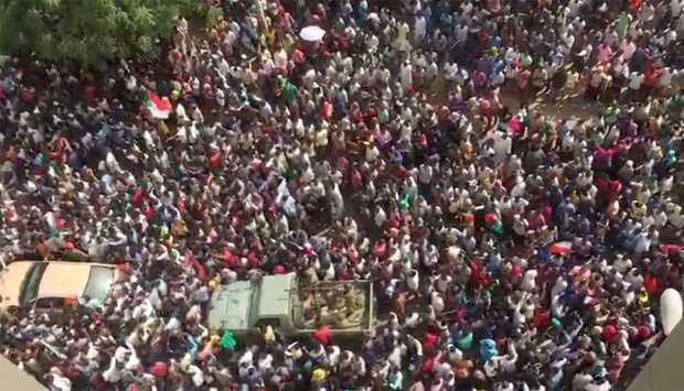 People are seen in the streets after televised statement by Defence Minister Awad Mohamed Ahmed Ibn