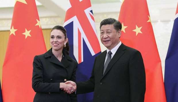 China's President Xi Jinping (R) shakes hands with New Zealand's Prime Minister Jacinda Ardern