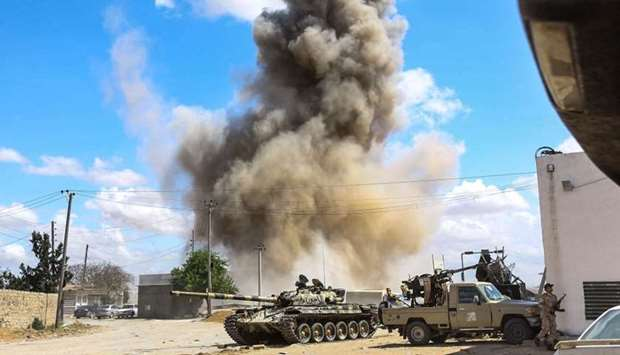 A smoke plume rising from an air strike behind a tank and technicals belonging to forces loyal to Li