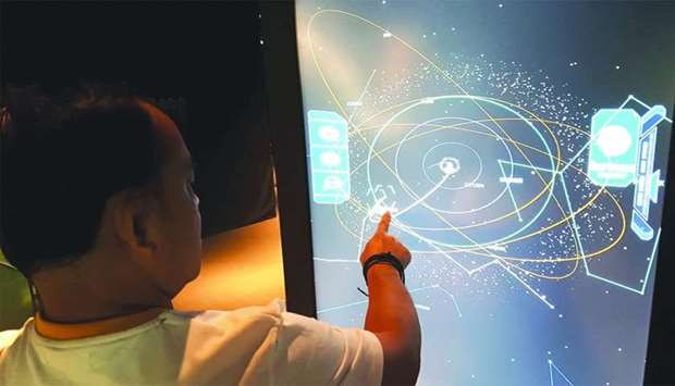 A visitors tries some of the interactive features of Al Thuraya Planetarium. PICTURE: Joey Aguilar