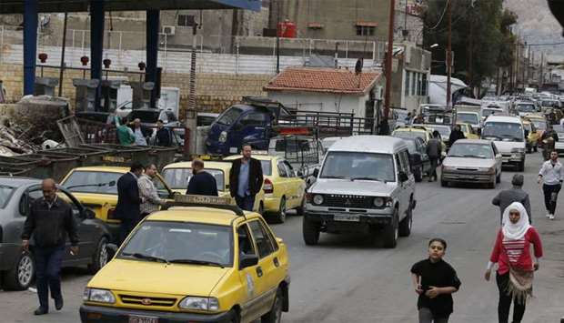 Drivers queue for gasoline in front of a petrol station in the Syrian capital Damascus