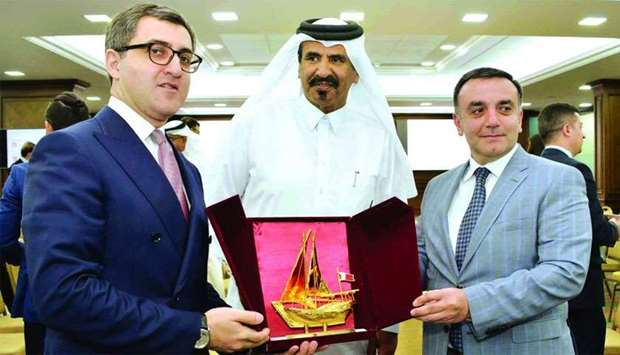 Al-Kuwari hands over a token of recognition to Oglu in the presence of Ismayilov.