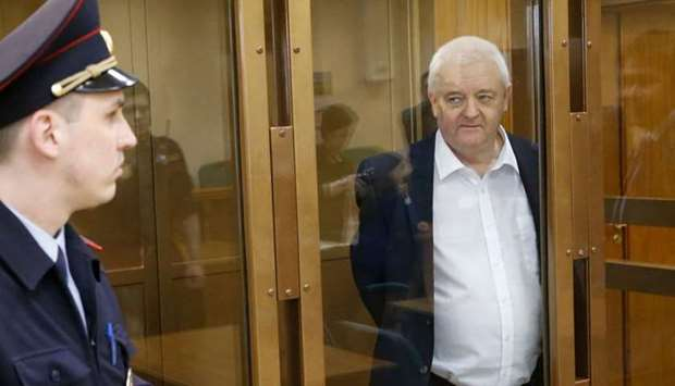 Frode Berg stands inside a defendants' cage as he waits to hear his verdict in Moscow