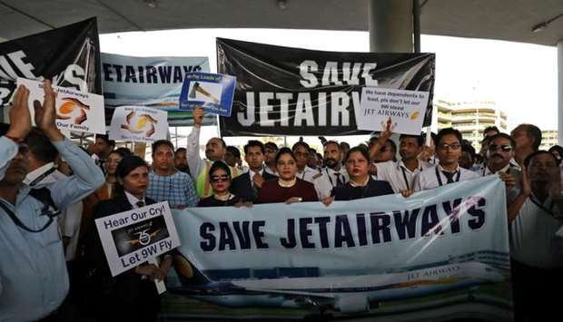Jet Airways employees hold placards and banners during a protest at the Indira Gandhi International