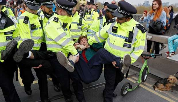 Police officers detain a climate change activist at Waterloo Bridge during the Extinction Rebellion