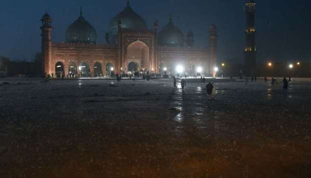 People arrive to pray at the historical Badshahi Mosque during heavy rain in Lahore yesterday.