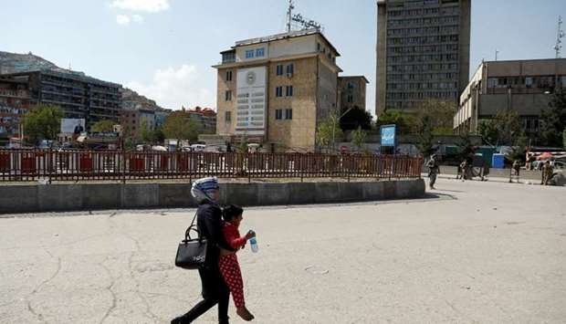 An Afghan woman carries a child rescued from the building of Ministry of Communication and Informati