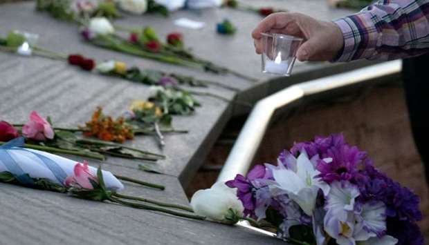 A visitor places a candle among flowers at the Columbine Memorial at Clement Park in Littleton