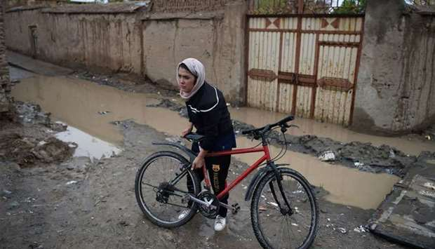Afghan cyclist Kobra Samim adjusts her bicycle on a street in Kabul. Across Afghanistan, women have