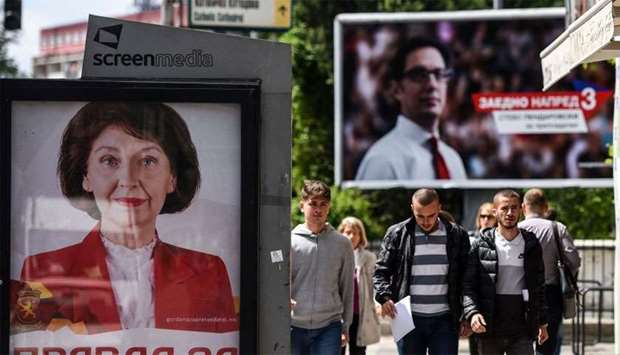 People walk past electoral posters of presidential candidates Stevo Pendarovski (R) from the ruling