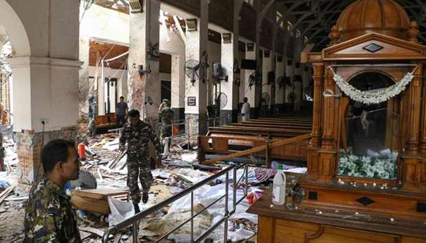 Sri Lankan security personnel walk past debris at St. Anthony's Shrine following an explosion