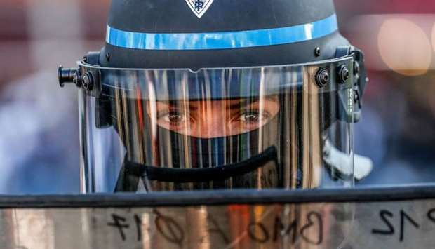 A police officer looks on from behind a riot shield during an anti-government demonstration called b