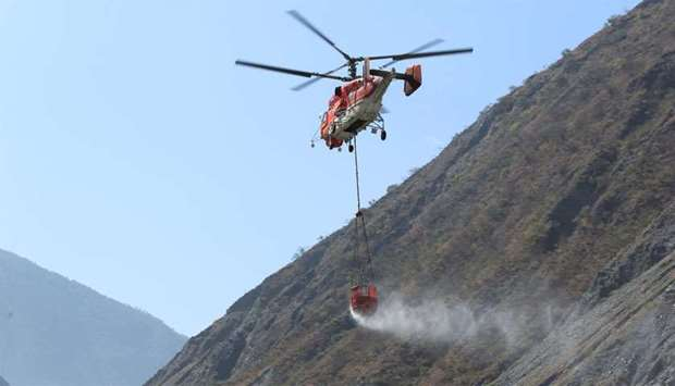 Helicopter carries water in a bucket to extinguish forest fire in Muli county, in Liangshan Yi Auton