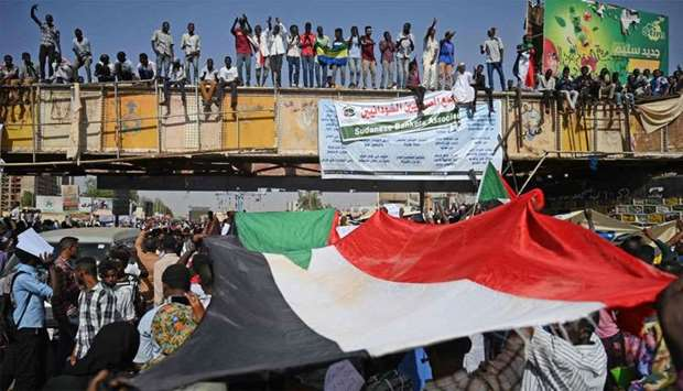 "Sudanese protesters wave the national flag during a ""million-strong"" march outside the army headquar"