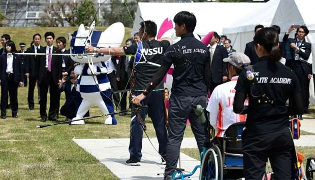 Archers shoot at targets as part of the opening ceremony of the Yumenoshima Park Archery Field, a ne