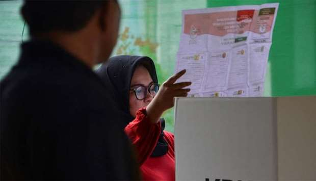 A woman looks at her ballot during a revote due to logistical issues in the country's general electi