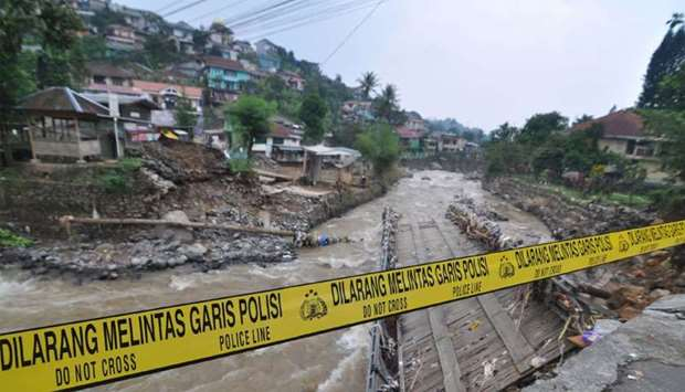 A police line is placed at a damaged bridge following torrential rain in Bogor, West Java