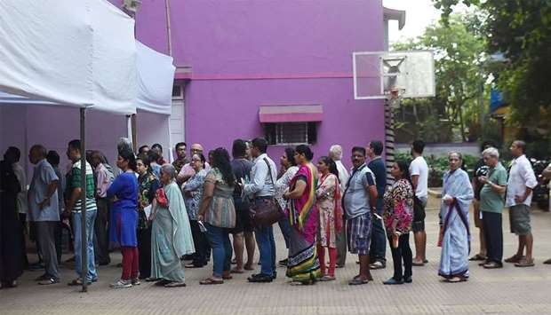 Indian voters wait for start of voting at a polling booth in Mumbai