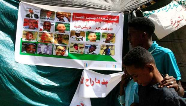 Sudanese protesters walk past a banner bearing the portraits of protesters, who died during the dead