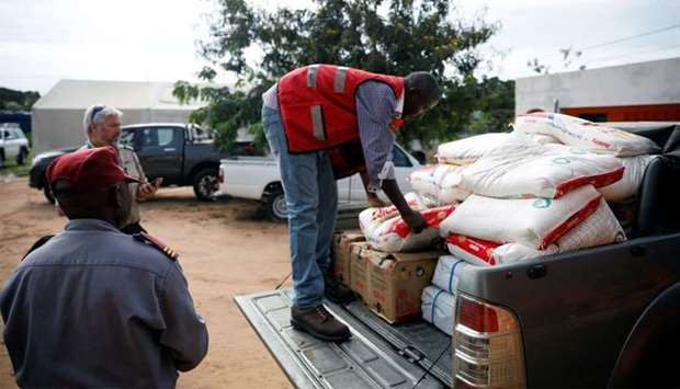 Aid workers load food onto a truck as flooding spreads in the aftermath of Cyclone Kenneth in Pemba,