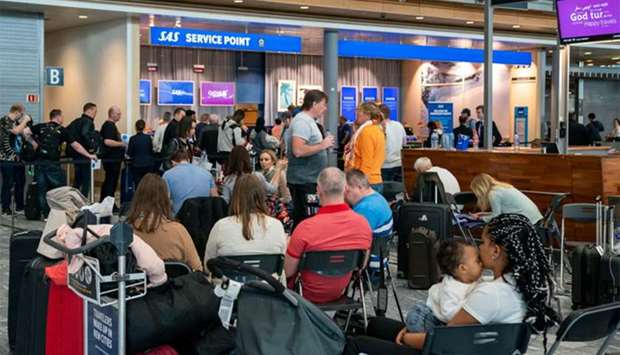 Passangers wait at the Scandinavian Airlines (SAS) counter at Oslo Airport in Gardermoen