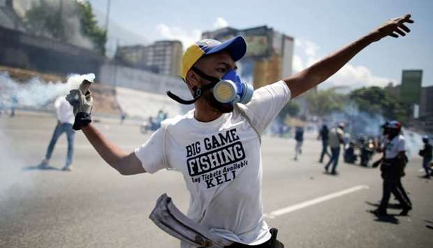 An opposition demonstrator throws back a tear gas canister on a street near the Generalisimo Francis