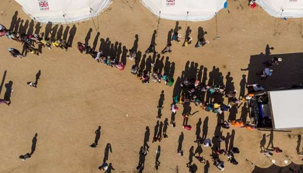An aerial view taken in Beira, Mozambique, on April 1, 2019 shows displaced people queuing for suppl