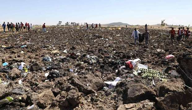 Rescue teams collect bodies in bags amid debris at the crash site of Ethiopia Airlines near Bishoftu