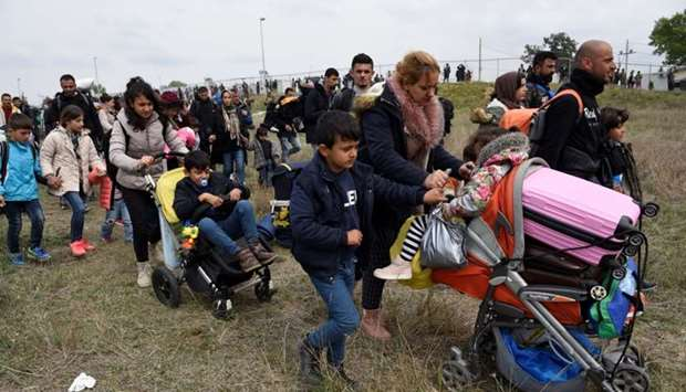 A woman pushes a pram as migrants and refugees walk away from a camp near the town of Diavata in nor