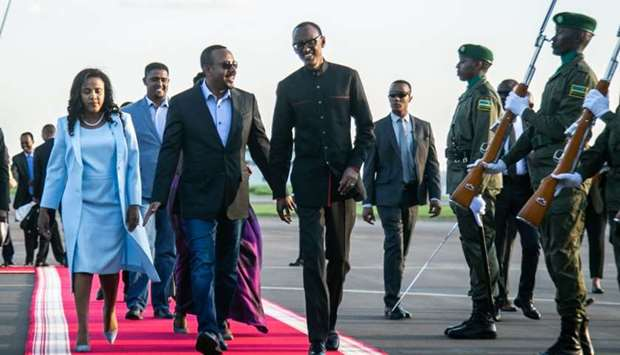 Rwanda's President Paul Kagame (R) welcomes Ethiopia's Prime Minister Abiy Ahmed who will attend for