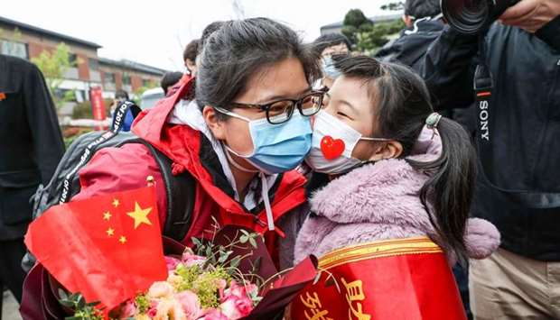 A member (L) of a medical assistance team from Huaian being welcomed by her daughter after returning