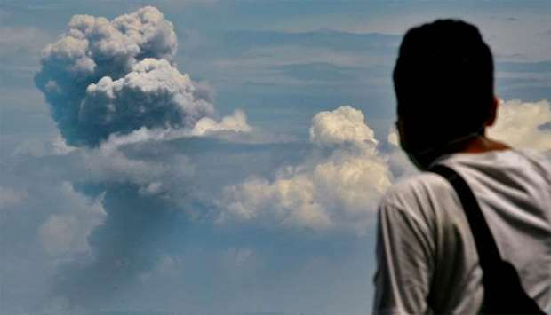 A man watches Krakatau spewing ash during an eruption, in Serang, Indonesia's Banten province