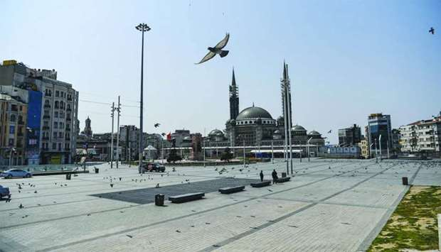 Pigeons fly over the empty Taksim square in Istanbul