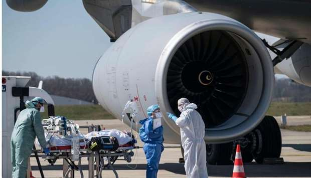 Medical staff embark a patient infected with the COVID-19 onboard Airbus A330 Phenix aircraft