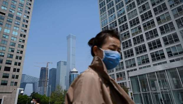 A woman wearing a face mask walks in the Central Business District (CBD) in Beijing