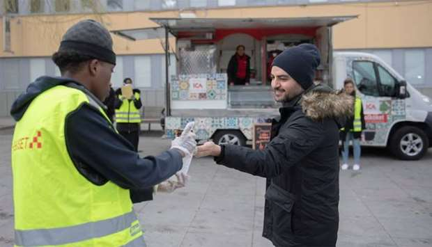 A young volunteer wearing gloves offers hand sanitizer during an information campaign about the coro