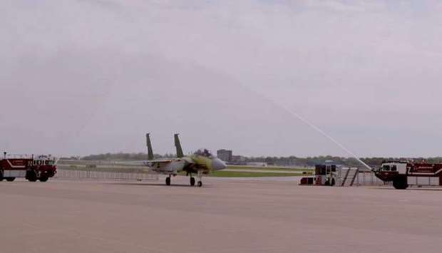 A F-15 fighter developed for the Amiri Air Force is welcomed with a water cannon salute at a US base