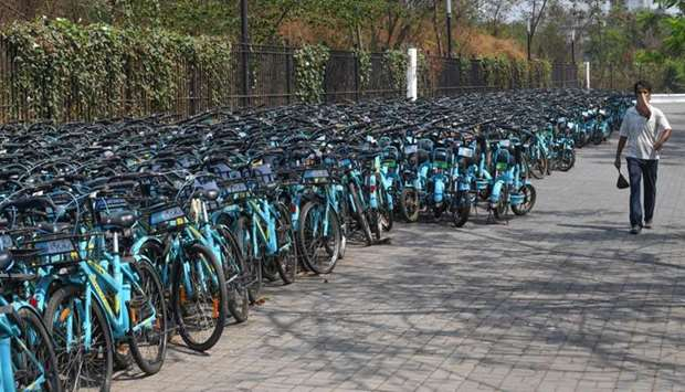 A man walks past rental bicycles stacked outside a a park during a government-imposed nationwide loc